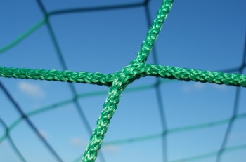 perspective shot of green soccer net against clear blue sky
